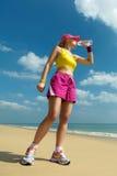 Питьевая вода женщины фитнеса после бежать на пляже. Стоковое Изображение