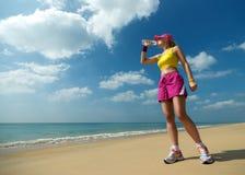 Питьевая вода женщины фитнеса после бежать на пляже. Стоковые Изображения RF