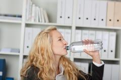 Питьевая вода коммерсантки от бутылки Стоковые Изображения