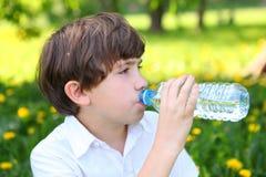 Питьевая вода мальчика от бутылки внешней Стоковые Фотографии RF
