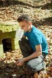 Питьевая вода мальчика подростка от колодца Стоковая Фотография