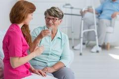 Питьевая вода медсестры с старшей женщиной стоковые фотографии rf
