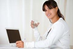 Питьевая вода молодой женщины на офисе Стоковое фото RF