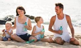 Питьевая вода семьи на пляже Стоковое Фото