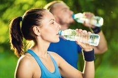 Питьевая вода человека и женщины от бутылки позже стоковая фотография rf