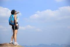 Питьевая вода hiker женщины на горе захода солнца Стоковое Изображение RF