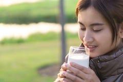 Питьевое молоко женщины крупного плана с счастливым bac природы стороны и зеленого цвета стоковое изображение rf