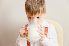 Питьевое молоко мальчика из больших кружек стоковая фотография rf