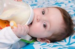 Питьевое молоко младенца от бутылки Стоковая Фотография