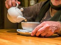 Питье бака чая взгляда крупного плана лить в чашку в старших руках Стоковое Изображение