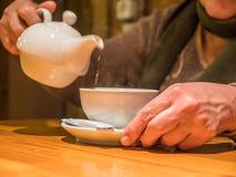 Питье бака чая взгляда крупного плана лить в чашку в старших руках Стоковые Фото