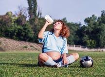 Питье беременной женщины на футбольном поле стоковое фото