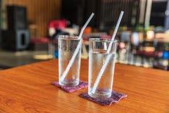 Питье воды в стекле на таблице Стоковые Изображения RF
