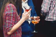 Питье владениями молодой женщины в баре Стоковые Фото
