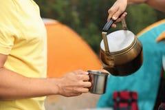 Питье женщины лить в кружку для человека outdoors стоковое фото rf