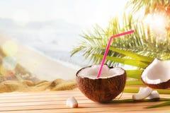 Питье кокоса в плодоовощ кокоса на таблице на тропическом пляже Стоковые Изображения