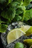 Питье коктеиля Mojito с известкой, льдом и мятой Стоковые Фото