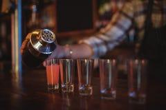 Питье коктеиля кельнера лить в стопки на счетчике стоковые изображения rf