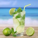 Питье коктеиля Mojito или Caipirinha на пляже Стоковое фото RF