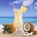 Питье коктеиля Pina Colada на пляже Стоковые Фото