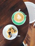 Питье кофе (плоско белое) и десерт голубик-кокоса на таблице Стоковое Фото