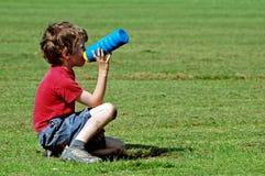 питье мальчика имея парк Стоковые Изображения RF
