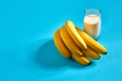 Питье молока банана и пук бананов на голубой предпосылке Стоковая Фотография RF