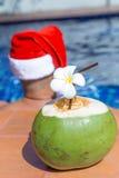 Питье сока кокоса с шляпой Санты рождества человека Стоковые Фотографии RF