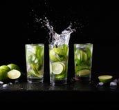 Питье спирта коктеиля традиционного пляжа Mojito освежая в стекле с выплеском, водой соды подготовки бара, известкой, мятой Стоковые Фото