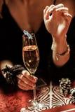 Питье удерживания женщины с обломоком покера в казино Стоковое Изображение