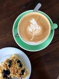 Питье эспрессо (плоско белое) и десерт голубик-кокоса на таблице Стоковые Фотографии RF