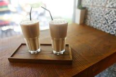 2 питья кофе внутри в стеклянной чашке с стойкой выпивая соломы дальше Стоковые Изображения RF