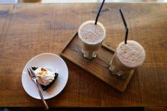 2 питья кофе с выпивая соломой и куском пирога на поддоннике Стоковая Фотография RF