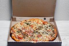 Пицца в картонной коробке на белой деревянной предпосылке над взглядом Поставка пиццы Меню пиццы стоковое фото rf