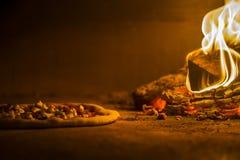 Пицца в печи деревянного огня стоковые фото