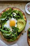 Пицца завтрака с испеченным яичком и зелеными цветами стоковая фотография rf