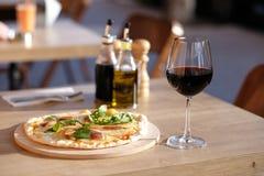 Пицца и красное вино в ресторане стоковая фотография rf