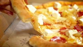Пицца конца-вверх очень вкусная лежит на таблице пока руки отделяют вкусные куски с сыром и мясом на ем, фаст-фуде сток-видео