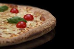 Пицца макроса на черной предпосылке с томатами и базиликом вишни Стоковое Изображение
