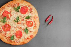 Пицца Маргариты с томатом и красным chili 2 на серой таблице, взгляде сверху и месте для текста стоковые фото