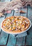 Пицца морепродуктов на деревенской деревянной таблице с раковинами Стоковое фото RF