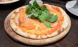 Пицца на деревянном подносе, на таблице Стоковое Изображение