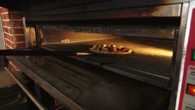 Пицца на специальном лопаткоулавливателе положена в печь видеоматериал