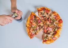 Пицца на таблице с рукой девушек Стоковые Фото