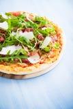 Пицца с ветчиной Пармы ветчины, arugula & x28; rocket& x29 салата; и пармезан на голубом деревянном конце предпосылки вверх Стоковые Изображения RF