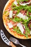 Пицца с ветчиной & x28; ham& x29 Пармы; , arugula & x28; rocket& x29 салата; и пармезан на темном деревянном взгляд сверху предпо Стоковое фото RF