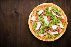 Пицца с ветчиной & x28; ham& x29 Пармы; , arugula & x28; rocket& x29 салата; и пармезан на темном деревянном взгляд сверху предпо Стоковые Изображения