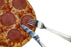 Пицца с вилкой и нож изолированный на белизне стоковая фотография