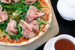 Пицца с салатом ростбифа и ракеты на таблице стоковые фотографии rf