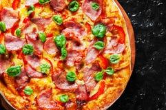 Пицца с сыром моццареллы, ветчиной, перцем, мясом, томатным соусом, специями и свежим базиликом Итальянская пицца на черноте стоковая фотография